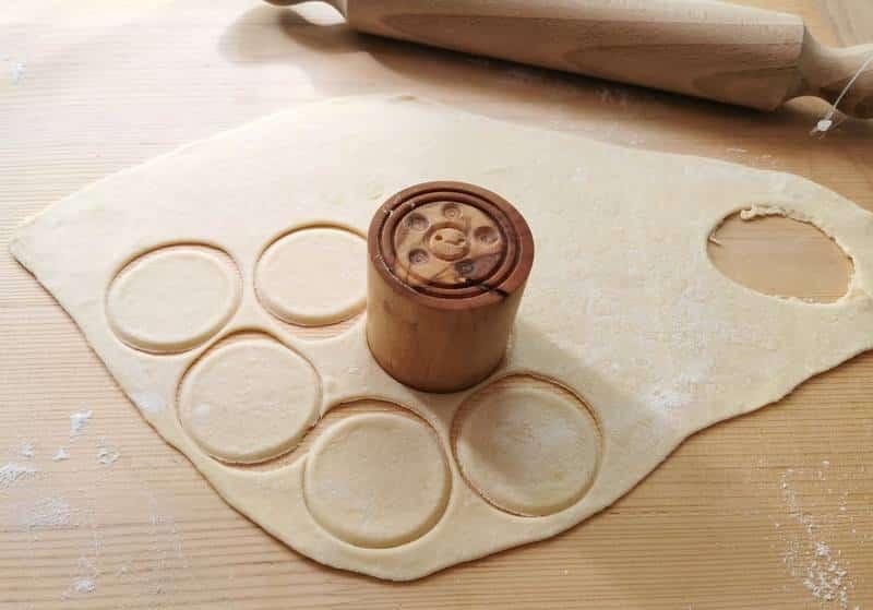 pasta discs cut out of dough using corzetti stamp