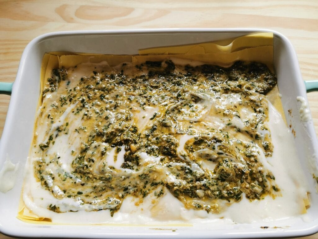 béchamel and pesto spread over lasagne sheets in oven dish