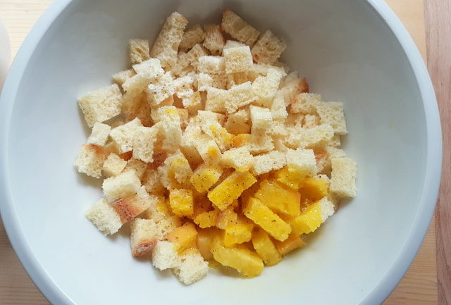 stale bread cubes in white bowl with beaten egg