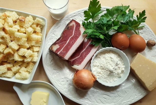 ingredients for canederli (Italian bread dumplings) on white plate