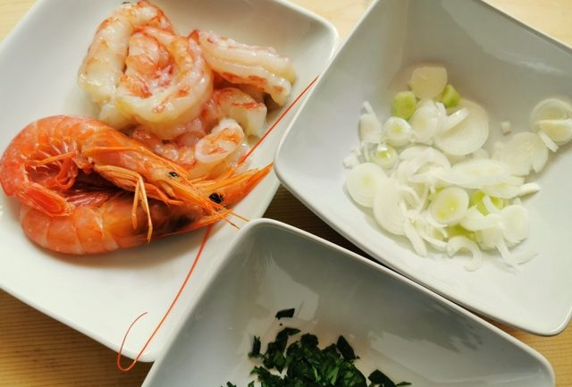 chopped spring onions in white bowl. Chopped parsley in white bowl. Prepared prawns in white bowl