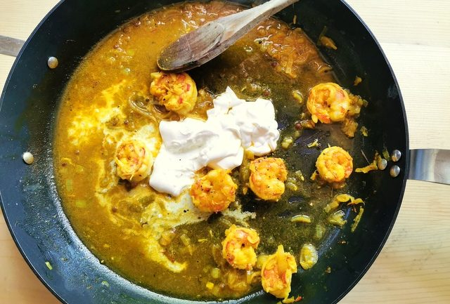 cooked peeled prawns in skillet with prawn saffron broth and heavy cream