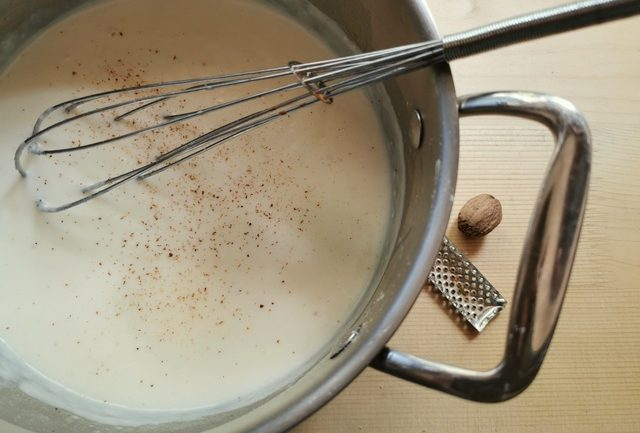 béchamel (white sauce) in saucepan with whisk
