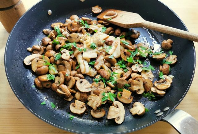 cremini and porcini mushrooms cooking in skillet with parsley and garlic