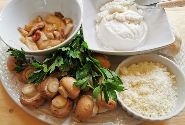 Ingredients for Italian ricotta mushroom lasagne al forno on white plate.