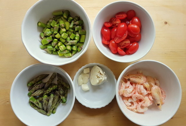 ingredients prepared for cooking chopped asparagus, separate asparagus tips, halved cherry tomatoes, cleaned shrimps and peeled garlic