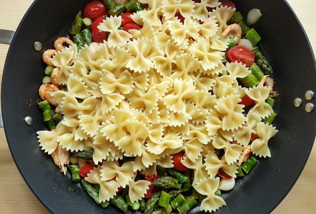 cooked farfalle pasta in frying pan with sauce ingredients