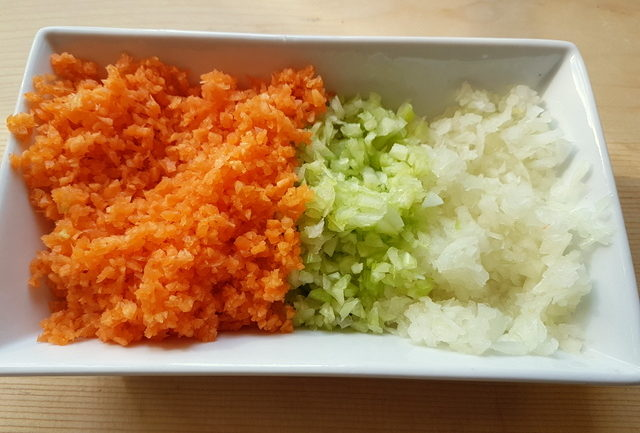 finely chopped onion, celery and carrots in a white bowl
