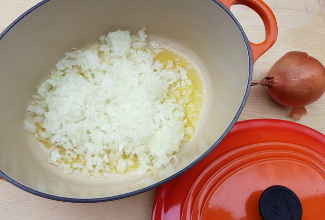 finely chopped onions cooking in Dutch oven with olive oil