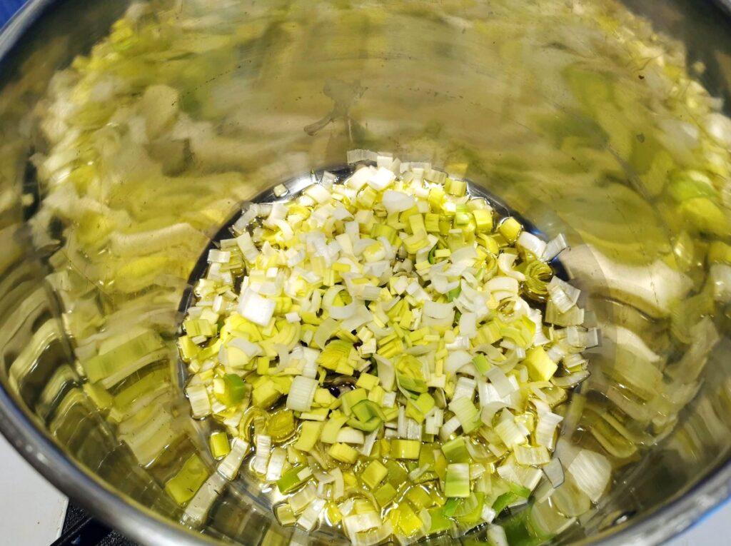 sliced leeks cooking in olive oil in large soup pot.