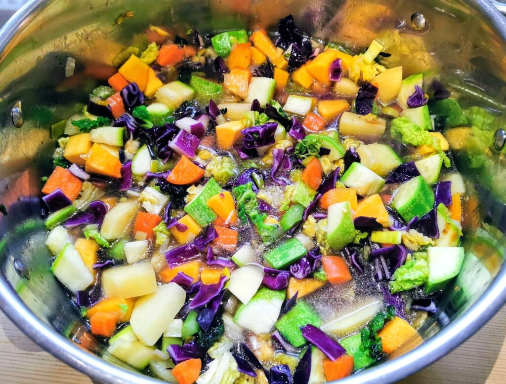 Minestrone vegetables cooking in water in large soup pot.