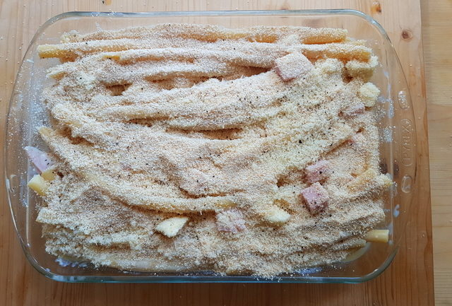 Neapolitan baked ziti pasta al gratin in oven dish before baking