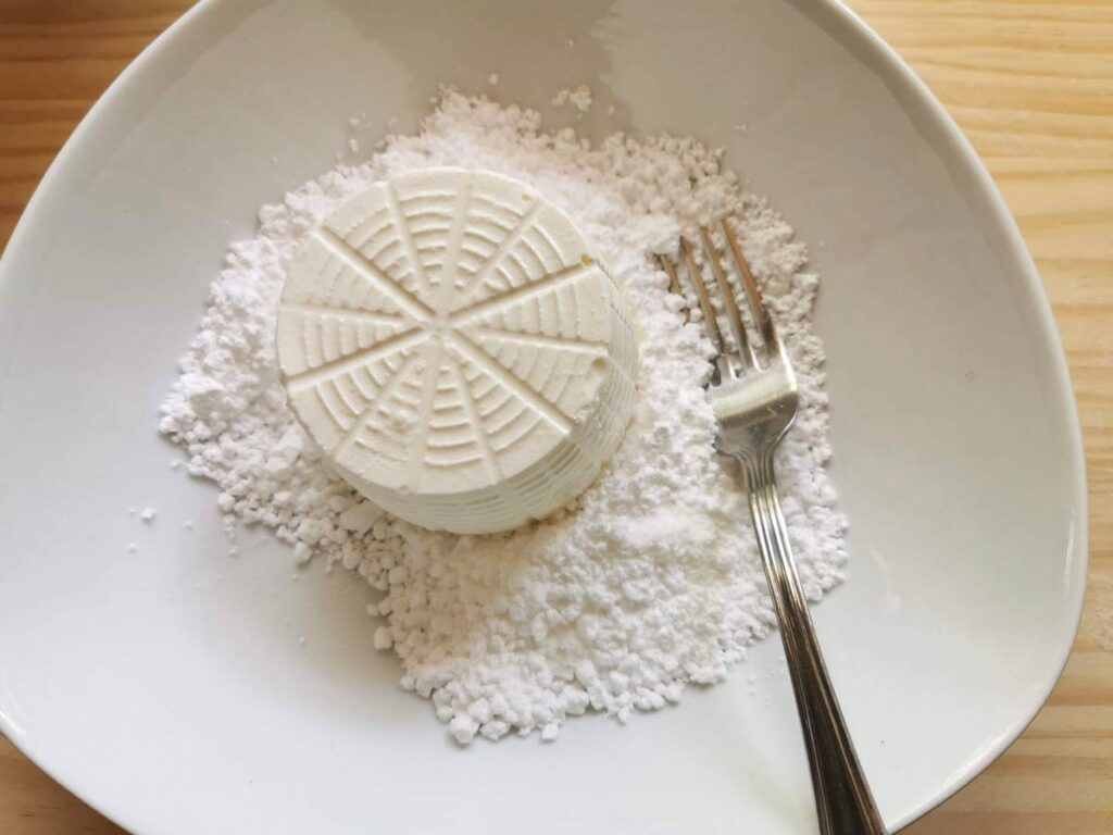 fresh ricotta and icing sugar in white bowl