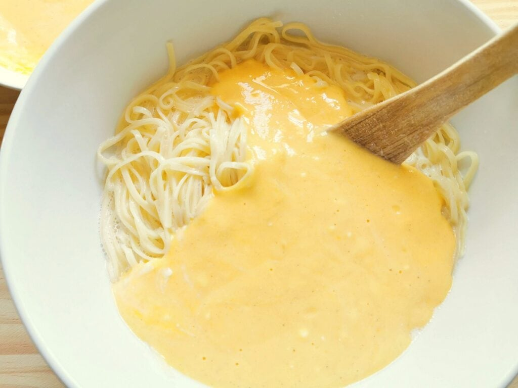 Ricotta and egg mixture added to the pasta and milk in white bowl