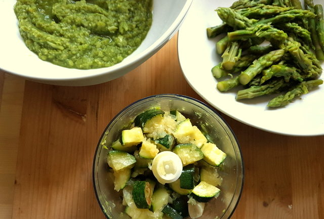 zucchini in blender bowl with asparagus spears and creamed asparagus in white bowls
