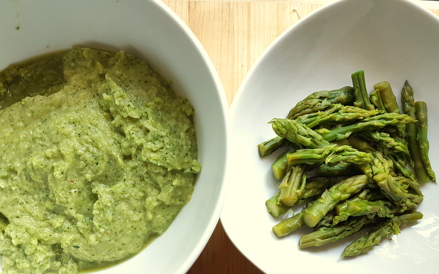 creamed asparagus pasta sauce in white bowl and asparagus spears in white bowl