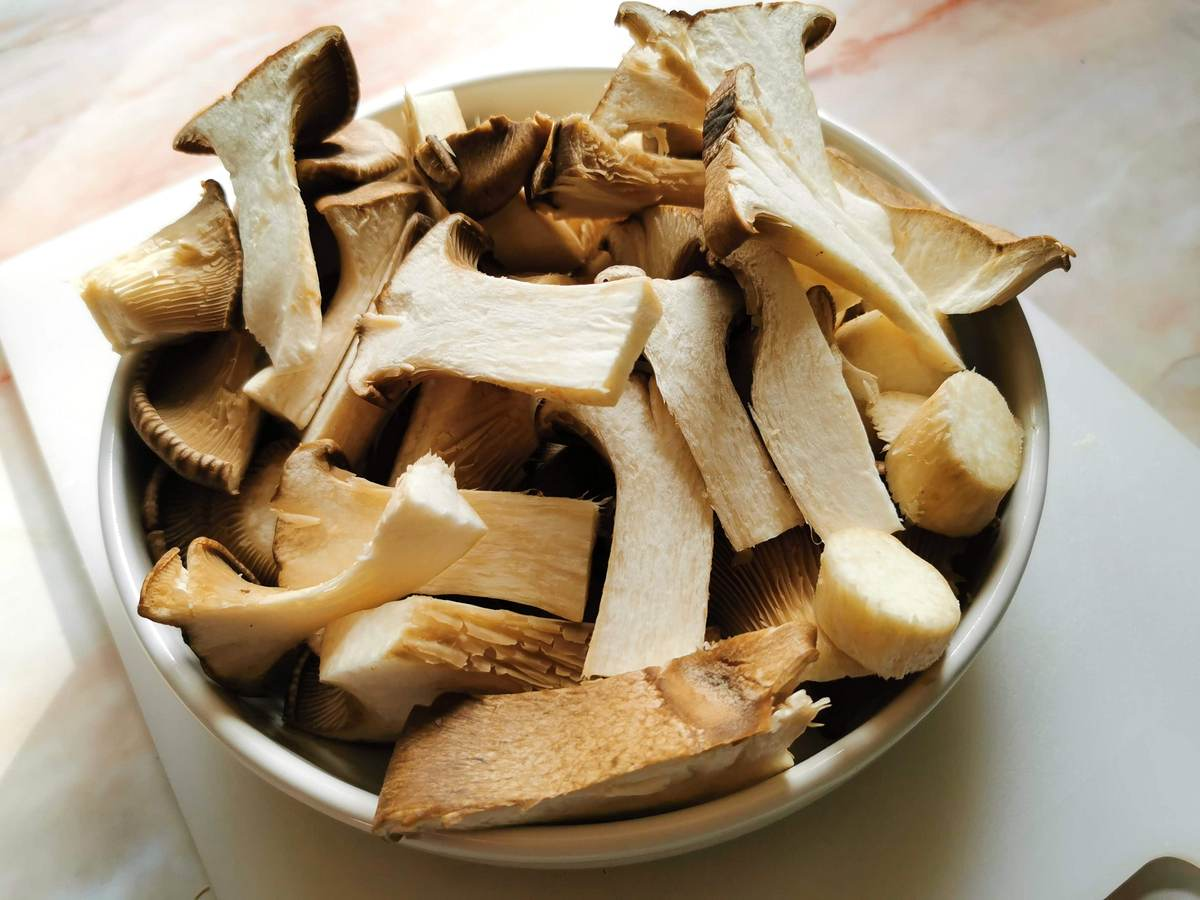 King oyster mushrooms ready cut in white bowl.