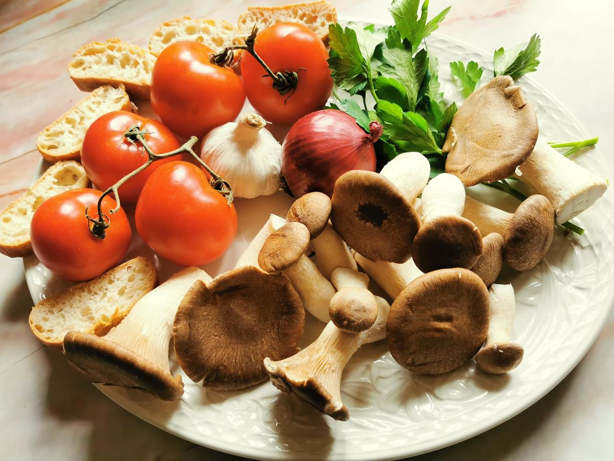 Ingredients for pasta with king oyster mushrooms on white plate