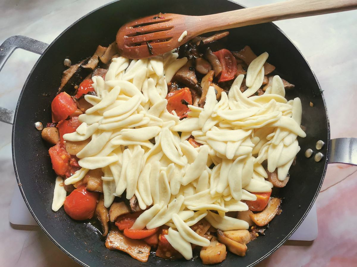 Cooked olive leaf pasta in skillet with king oyster mushroom sauce.
