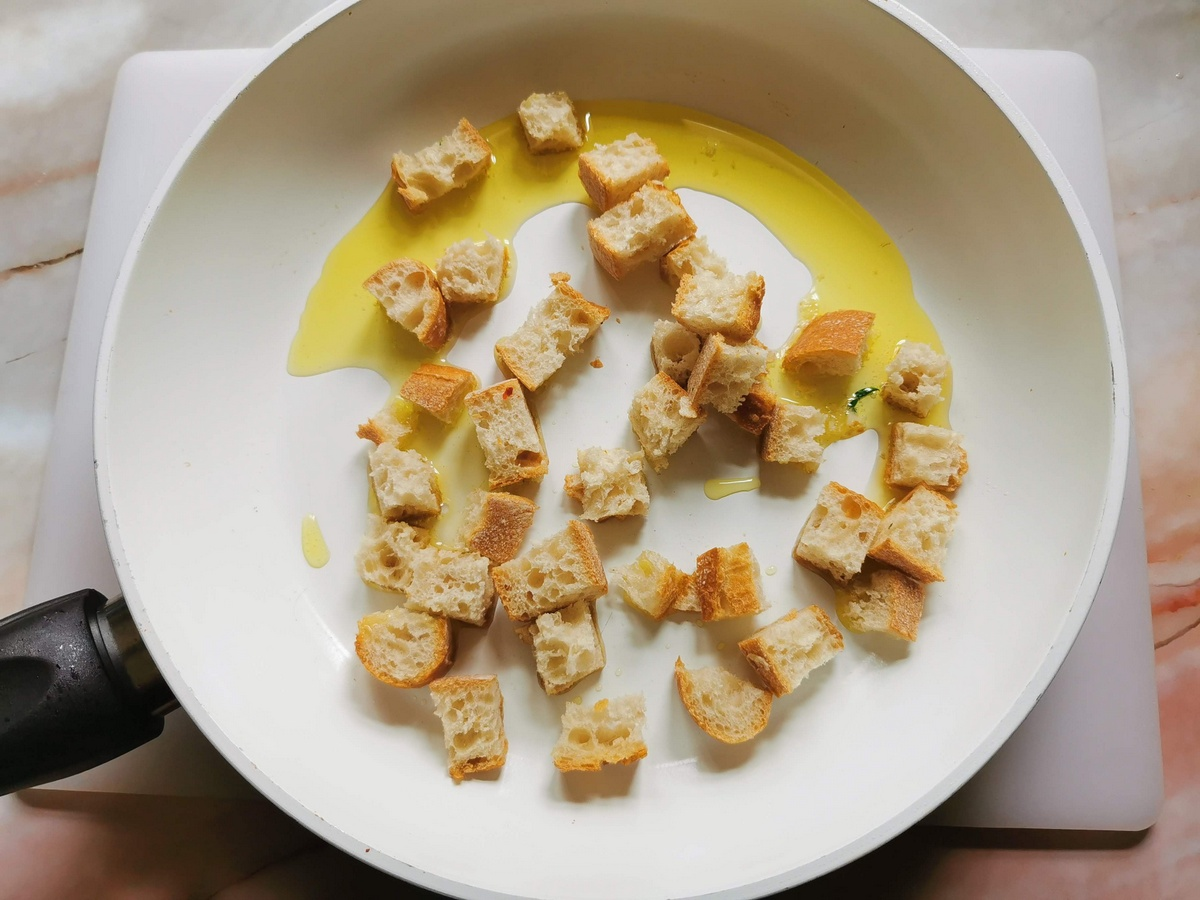 stale bread croutons in frying pan with olive oil.