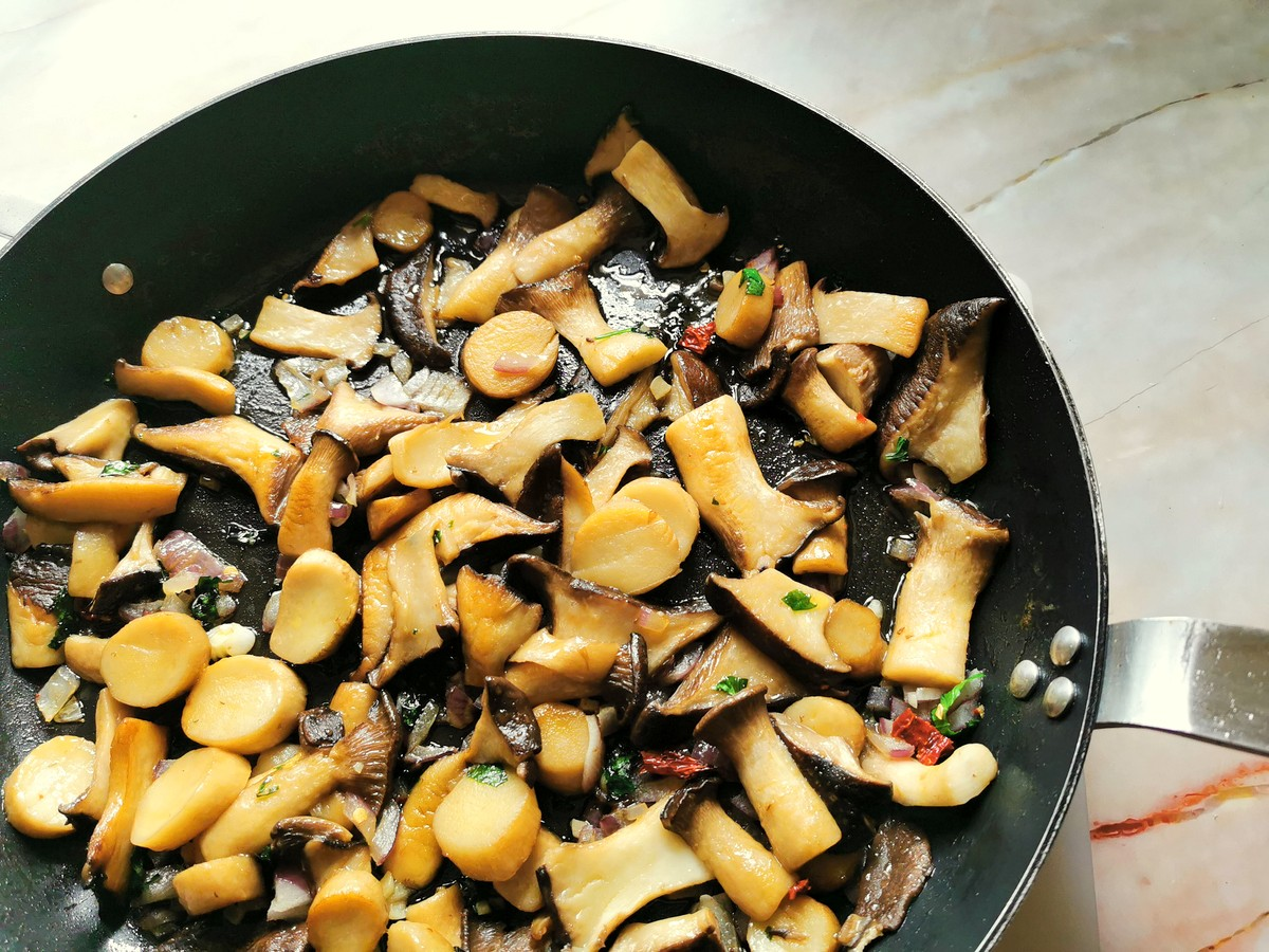 Cooked mushrooms in skillet with onions, garlic, peperoncino and parsley.