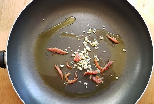 anchovie pieces and chopped garlic in frying pan