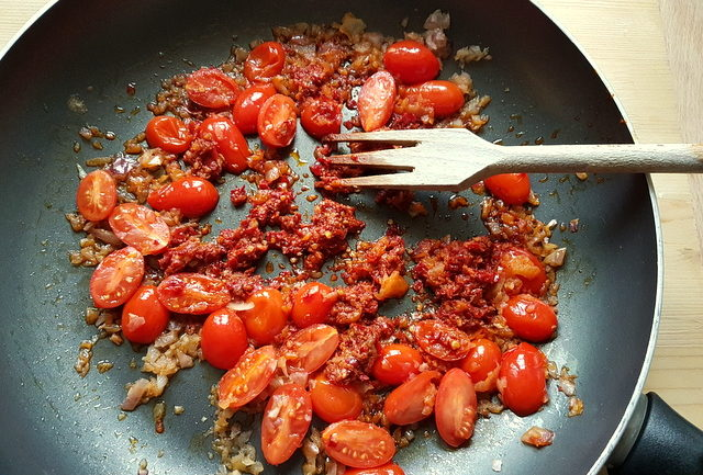 tomatoes, onions and nduja cooking in frying pan