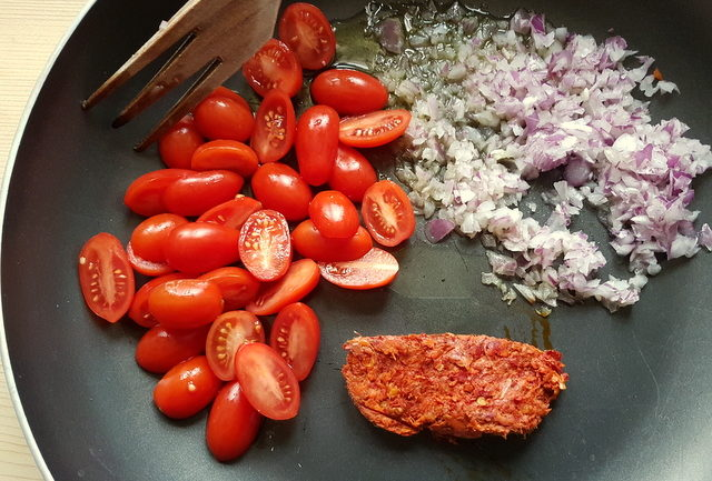 uncooked cherry tomatoes, onions and nduja in frying pan