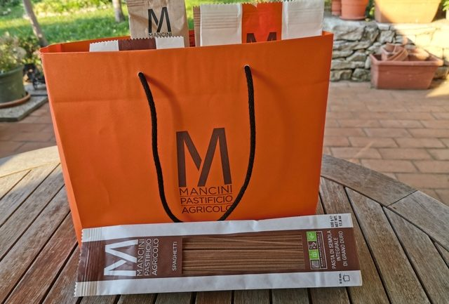 Pasta Mancini types of pasta in orange shopping bag on wooden table