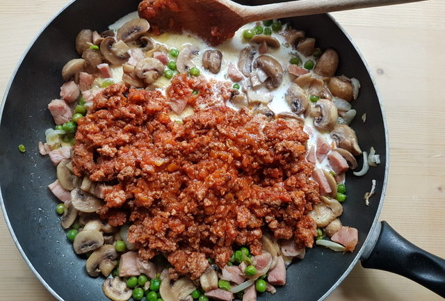 Bolognese sauce and cream added to mushroom, ham and pea sauce in deep frying pan