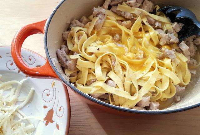 Tagliatelle pasta with cinnamon spiced pork ragu and raw eggs in Dutch oven