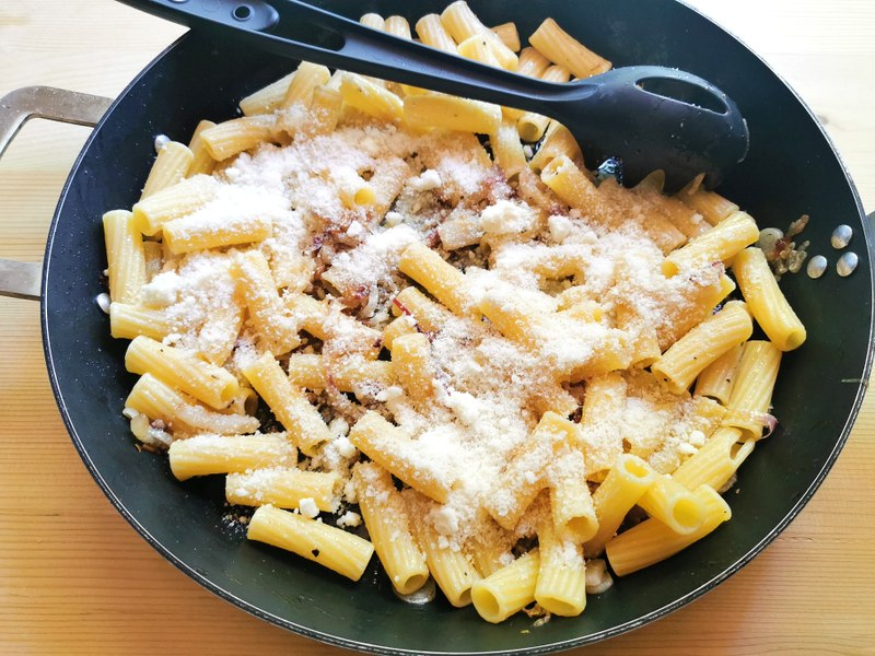 grated pecorino added to pasta, onions and lardo in skillet