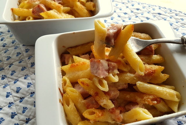 Penne pasta alla Valdostana baked in white oven dishes
