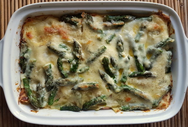 Baked poached salmon and asparagus lasagne al forno in white oven dish