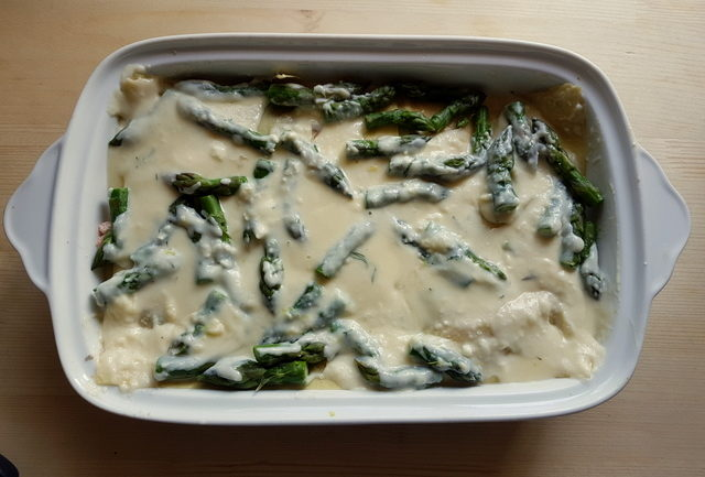 Poached salmon and asparagus lasagne al forno in white oven dish before baking