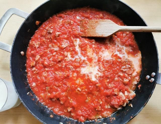 adding milk to the prosciutto ragu in skillet