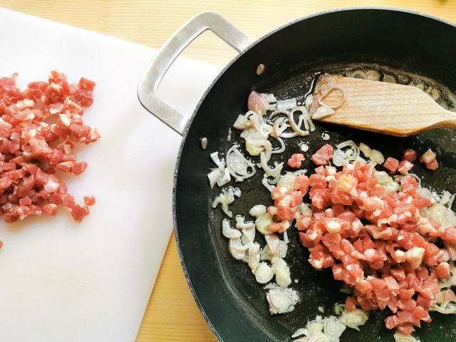 prosciutto pieces and chopped shallots frying in skillet