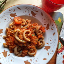Red lentil ragu with whole-wheat pasta in white and terracotta bowl