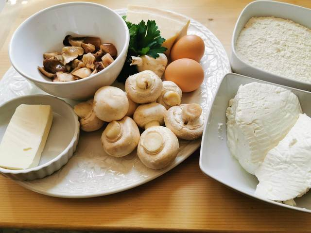 ingredients for ricotta gnocchi with mushrooms on white plate