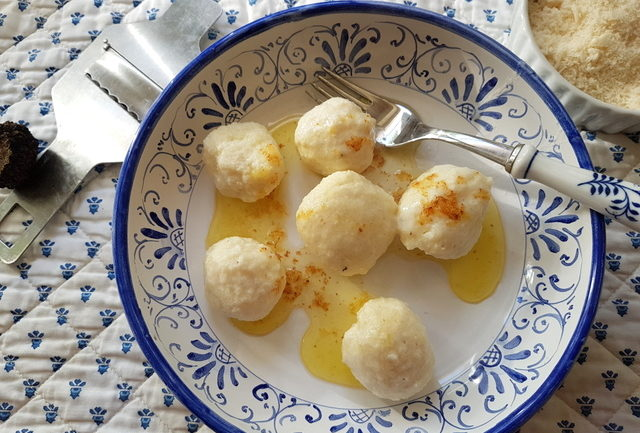 ricotta gnudi with browned butter on blue and white plate