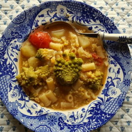Romanesco broccoli pasta soup in blue and white bowl