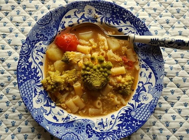 Romanesco broccoli pasta soup in blue and white bowl