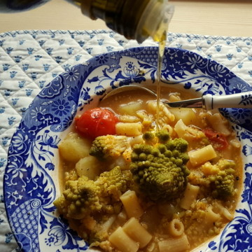 Romanesco broccoli pasta soup in blue and white soup bowl