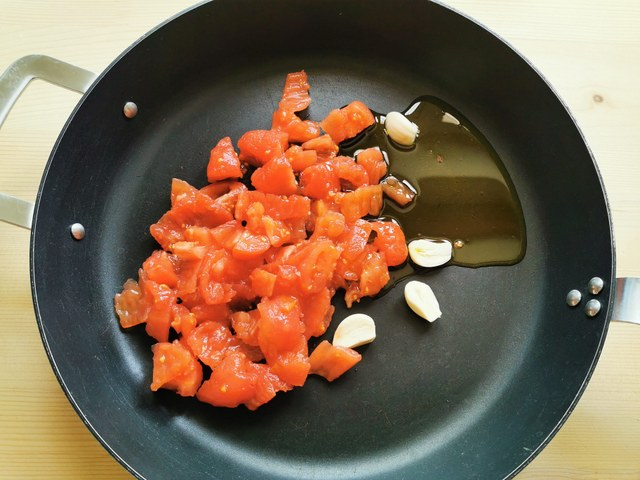 chopped fresh tomato pulp in skillet with garlic and olive oil