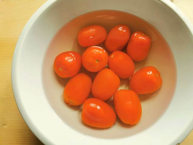 fresh ripe tomatoes in hot water in white bowl