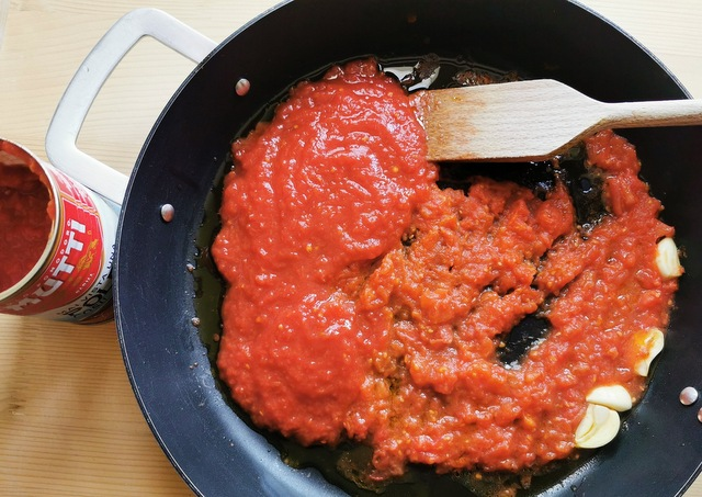 tomato passata and cooked fresh tomato pulp in skillet with garlic and olive oil