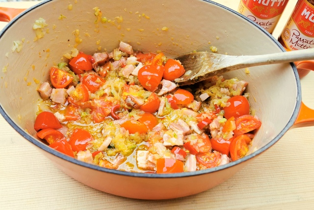 cherry tomatoes, pancetta and other ingredients cooking in Dutch oven