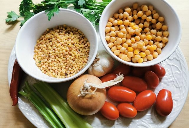 ingredients for fregola and chickpeas on white plate