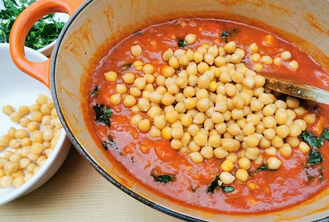 cooked chickpeas added to the fregola and sauce in a Dutch oven