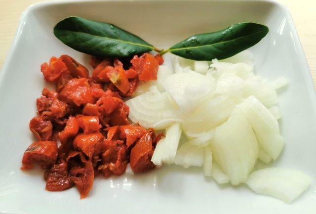 chopped onions and sun-dried tomatoes in white bowl with 2 bay leaves